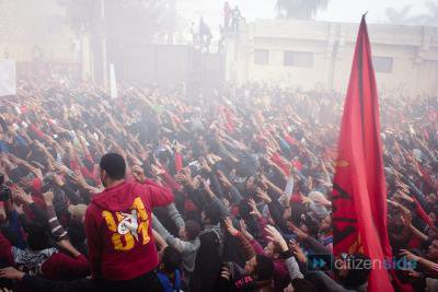 Crowd of men in mist with a large flag.  All hands raised in a salute.