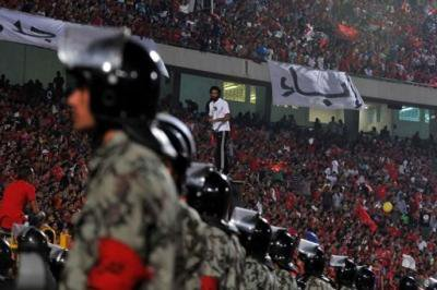 Line of police with the stadium crowd in the background.
