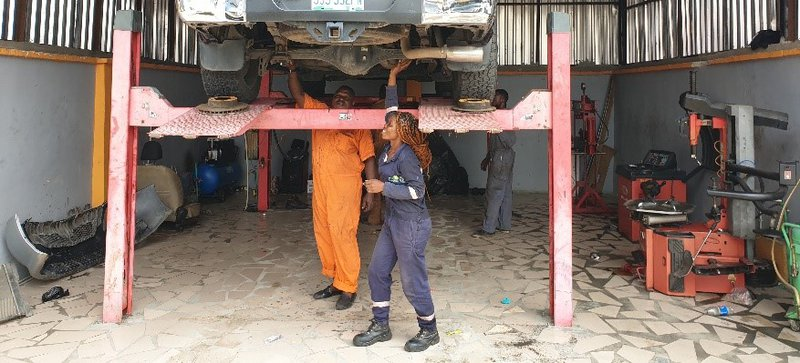 Florence Iria at work with car on lift