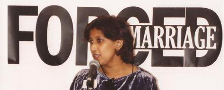 Woman speaking in front of a 'Forced Marriage' banner