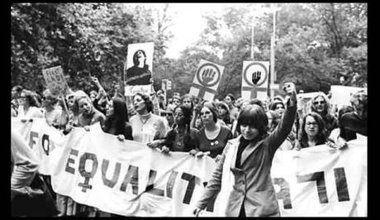 Women march behind 'March for Equality 1971' banner, while women at front raises her left fist