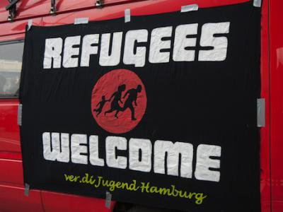 A sign welcoming refugees is hung from a school bus in Hamburg