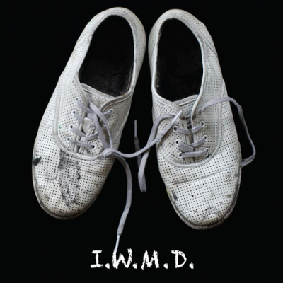 Dirty, white canvas shoes with 'I.W.M.D.' written underneath.