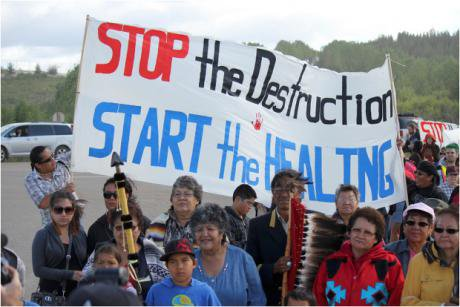 People hold a 'Stop the destruction - start the healing' banner