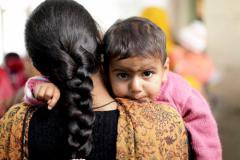 A Bangladeshi woman holds her baby daughter over her shoulder.