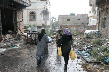 A soldier helps Reham Al-Bader and Naseem Al-Faqeeh to avoid snipers and landmines to distribute aid in Taiz.