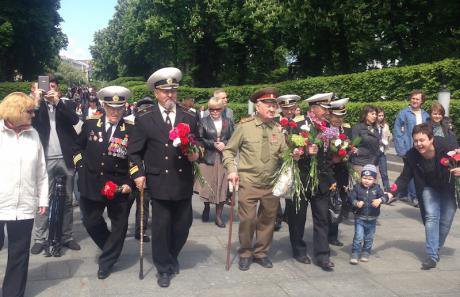 Veterans march to lay flowers at a monument to the dead.