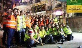 Posed group photo of about twenty young men in high-visibility jackets.