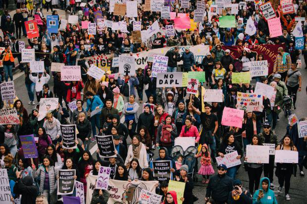 large demonstration of women protesting with placards