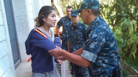 Karimova under house arrest arguing with members of the security services in 2014. She is wearing a hoody and running shorts.