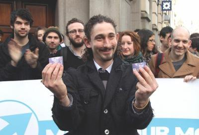 Man holds up two halves of a destroyed credit card, surrounded by campaigners