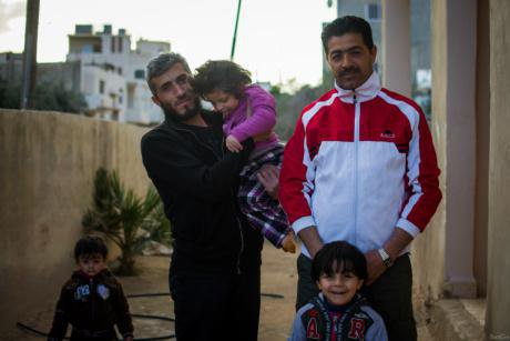 Naji Al Roahma with his two children and Syrian neighbors