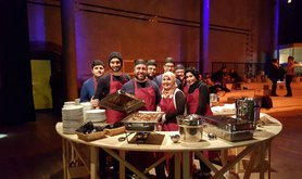 Malakeh and Mohammed serve Syrian food at an event.jpg