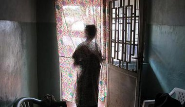 Woman stands at a window, silhouetted against curtain.