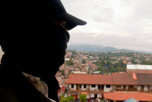 A masked man, member of the community police of Cherán, looks out from a church tower over the main square.