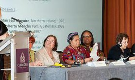 Six women seated on a panel, one standing at a podium.