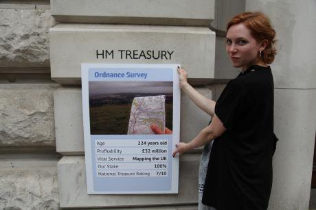 A woman holding a Top Trumps card showing the value of the Ordnance Survey.
