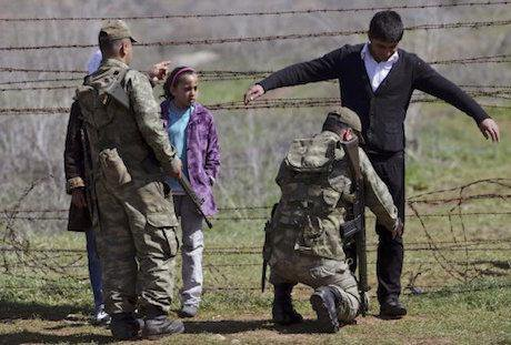 A Turkish soldier searches a young Syrian refugee at a border crossing. Burhan Ozbilici/Press Association. All rights reserved.
