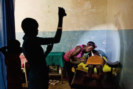 A midwife examines an expectant mother by torchlight. Julien Behal/PA Archive/PA Images. All rights reserved.