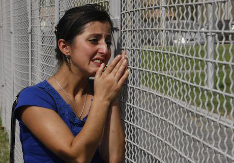 A woman cries at a prison fence as she and fellow protesters demand to see their family members during a protest rally against p
