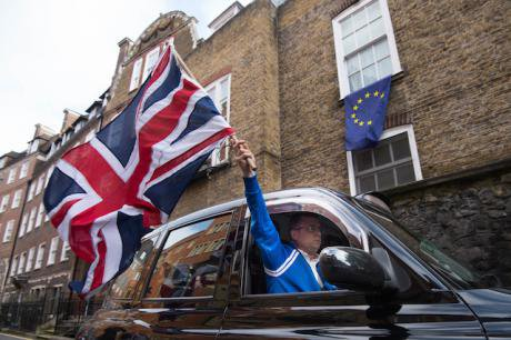 Taxi driver waves a Union Jack flag in Westminster, London after Britain voted to leave the European Union in an historic refere