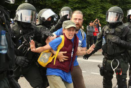 Two protesters in Hamburg are aggressively led away by a group of riot police