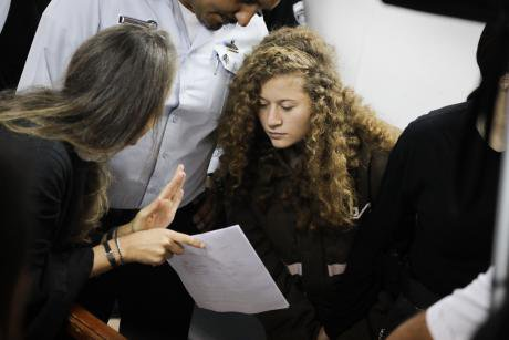 Ahed Tamimi talks with her lawyer at a military court in the West Bank.