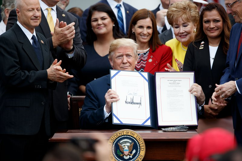 Donald Trump holds up a file that bears his signature
