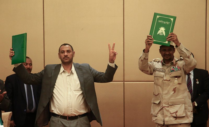 Two men, one in a military uniform, holding up green folders