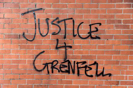Graffiti on a red brick wall. Reads Justice 4 Grenfell.