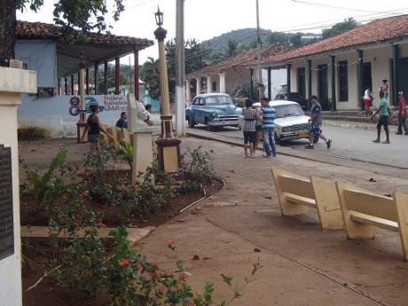 La Palma Park in Cuba with benches and passers by in sight