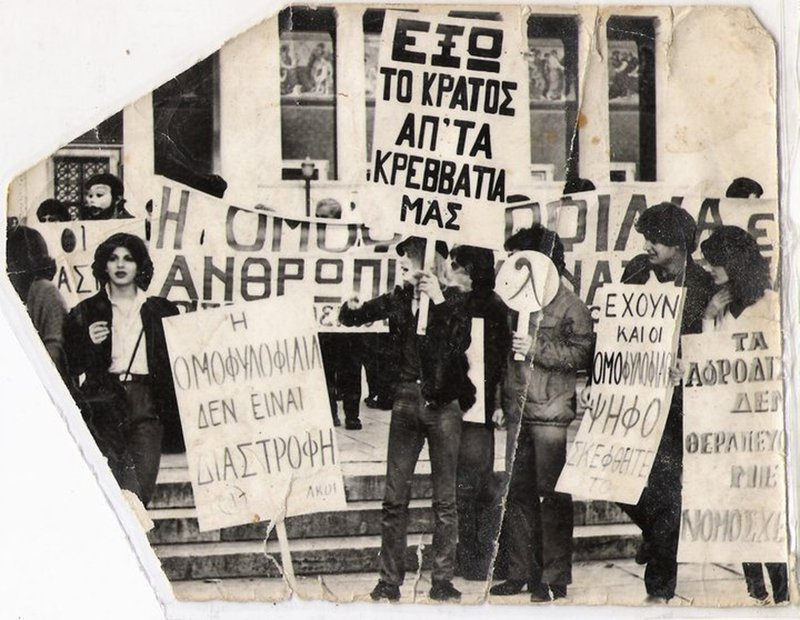 """Revenioti (centre) holds a placard that says """"(We want) the state out of our beds"""" at a 1981 demonstration in Athens."""