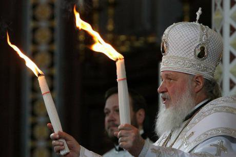 Patriarch Kirill holds up too flaming candles.