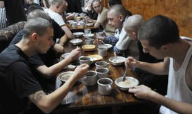 Shaven patients at City Without Drugs eat breakfast together.