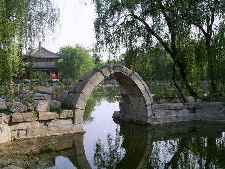 Pavillion and stone arch among the Old Summer Palace ruins. Wikimedia/Shizhao. Some rights reserved.