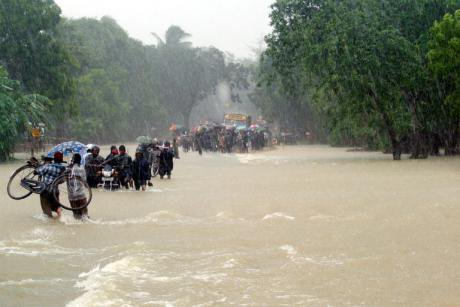 People,_bus_and_bike_in_rain_and_floodwater.jpg