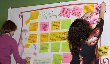 Women adding their personal commitment notes to a display board.