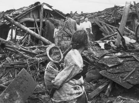 People surrounded by a devastated city.