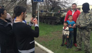 A family poses for pictures with a masked and uniformed man in front of an APC.