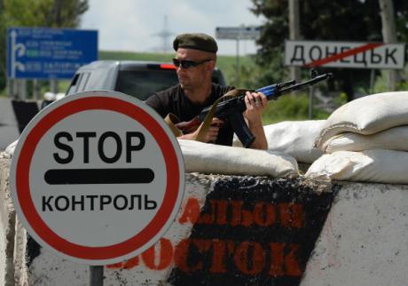 А member of the Vostok Battalion guards a roadblock at the entrance to Donetsk