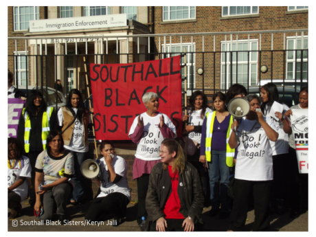 Women demonstrating with a Southall Black Sisters banner and megaphone
