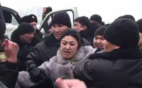 Police arrest a woman at an unsanctioned protest of Kazakhstan's currency devaluation. 15