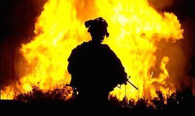Soldier watches a blaze in Iraq, 2008. David Marshall. The US Army/Flickr. Some rights reserved.