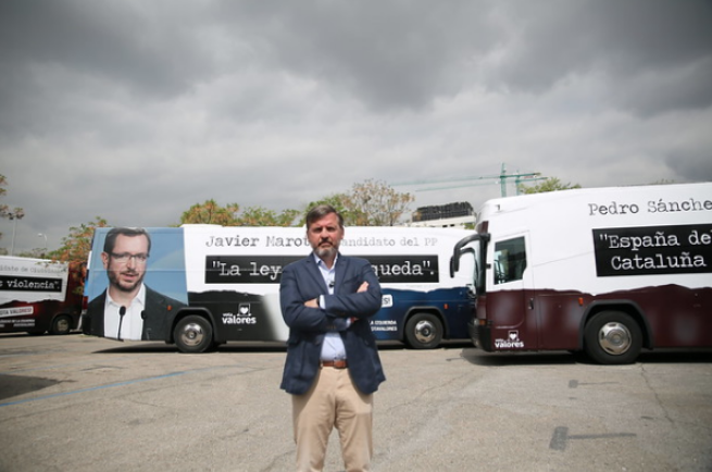 Ignacio Arsuaga in front of buses carrying ads against Vox's opponents