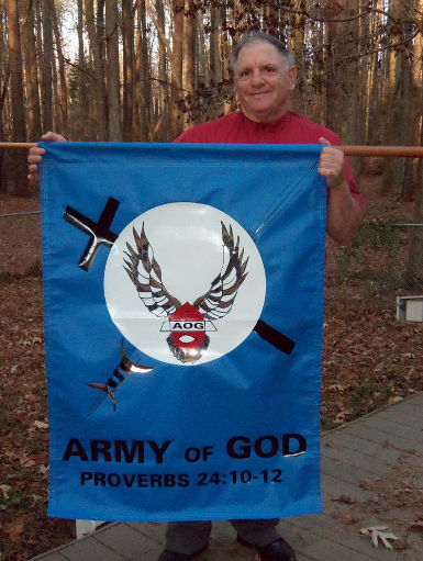 Donald Spitz holds Army of God banner.
