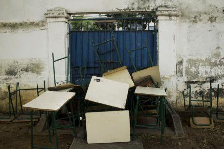 Desks and chairs piled up in front of the inside of the school gates, as a barricade