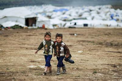 Syrian boys, whose family fled their home in Idlib, walk to their tent, at a camp for displaced Syrians, in the village of Atmeh, Syria, Monday, Dec. 10, 2012_0_1.jpg