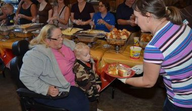 Woman handing a woman and child a plate of food.