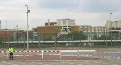 Industrial building with policeman standing outside. Workers standing on a balcony.