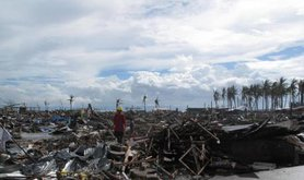 A man stands surrounded by the devastation wrought by Typhoon Haiyan in the city of Tacloban, Philippines